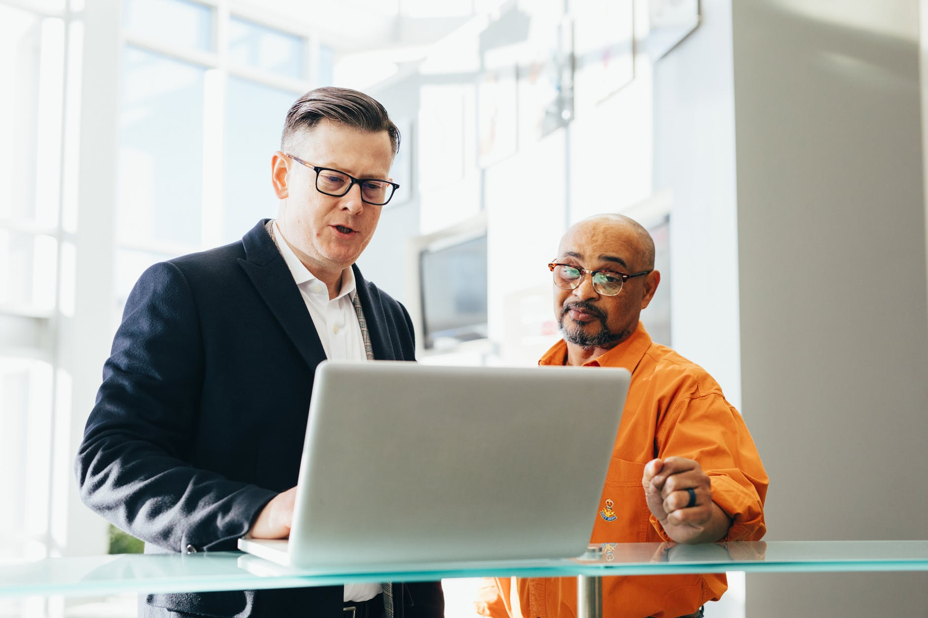 Two men stand at a computer discussing how to get technical support from briskData